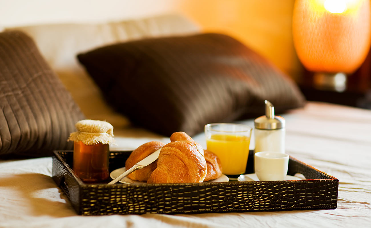 Tray on the bed with brioche, orange juice, honey and coffee